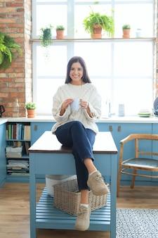 キッチンで温かい飲み物を飲む美しい若い女性