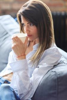 ソファで温かい飲み物を飲む美しい若い女性