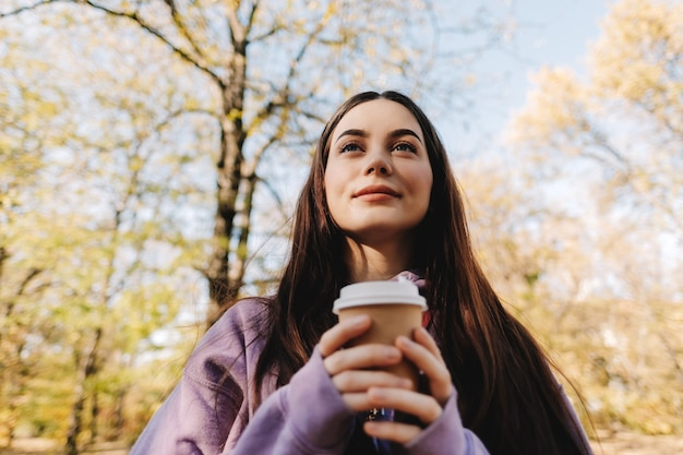 Красивая молодая женщина пьет кофе и наслаждается осенней погодой в парке.