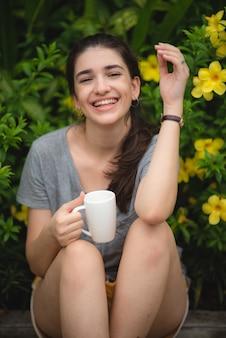 Красивая молодая женщина пьет кофе в саду