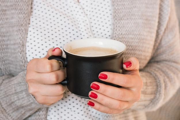 コーヒーカプチーノ、完璧な赤いジェルラッカーマニキュアを飲む美しい若い女性。