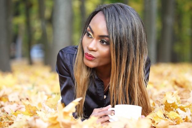 Красивая молодая женщина пьет кофе из белой чашки на осенних листьях в парке