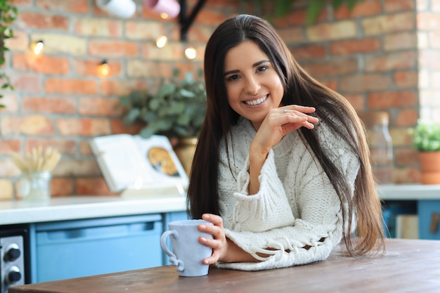 Beautiful young woman drinking coffee or tea in the kitchen