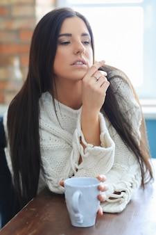 Bella giovane donna che beve caffè o tè in cucina