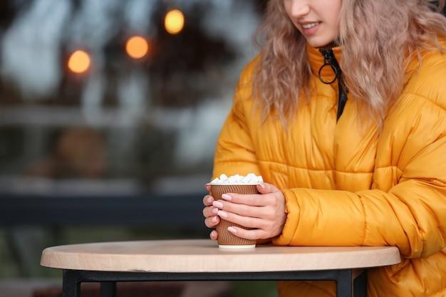 야외 카페에서 뜨거운 코코아를 마시는 아름 다운 젊은 여자