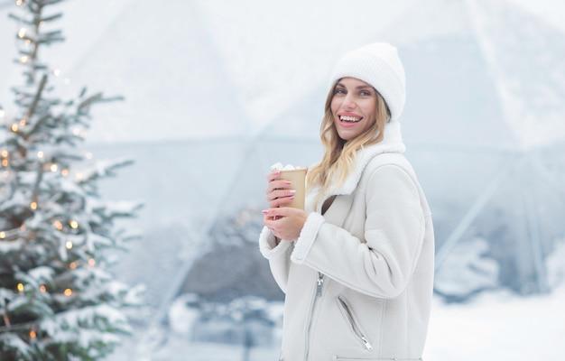 屋外でホットココアを飲む美しい若い女性。クリスマス。