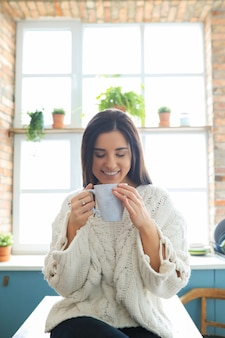 Bella giovane donna che beve una bevanda calda in cucina