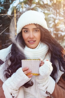Beautiful young woman drinking hot drink in winter forest