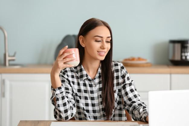Красивая молодая женщина пьет чай и использует ноутбук на кухне