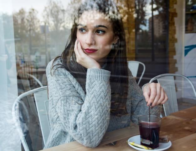 コーヒーショップで紅茶を飲む美しい若い女性。