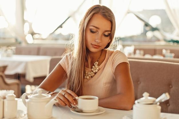 レストランでお茶を飲む美しい若い女性。