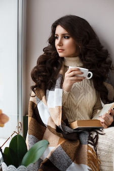 Beautiful young woman drinking tea and reading a book, covered with a warm blanket,dressed in a white knit dress at the window.