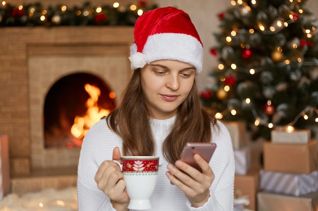 Beautiful young woman drinking tea, wearing santa hat and sweater, using her mobile phone in christmas, reading news from social networks, looks calm and concentrated, poses in decorated living room.
