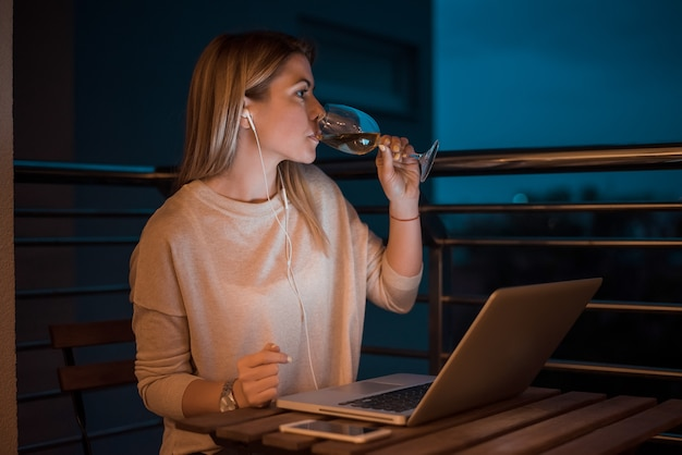 Beautiful young woman drinking wine while working on laptop at night. high iso image.