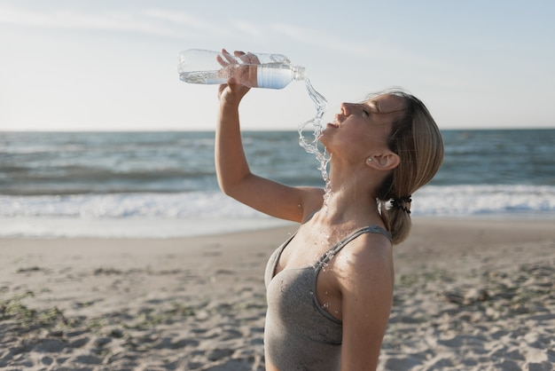 Beautiful young woman drinks water after a workout