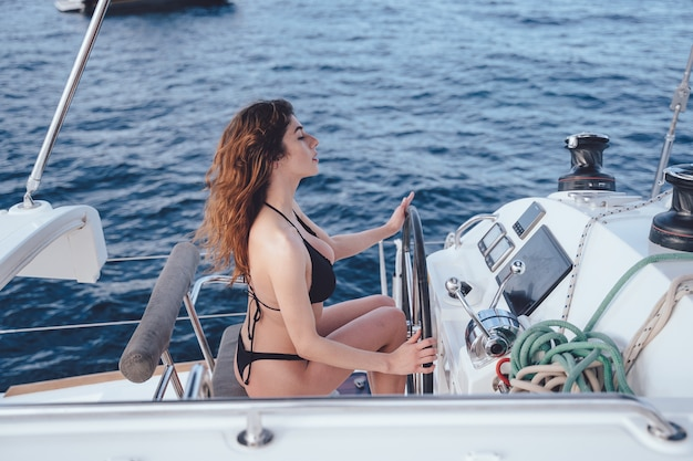 Красивая молодая женщина за рулем яхты