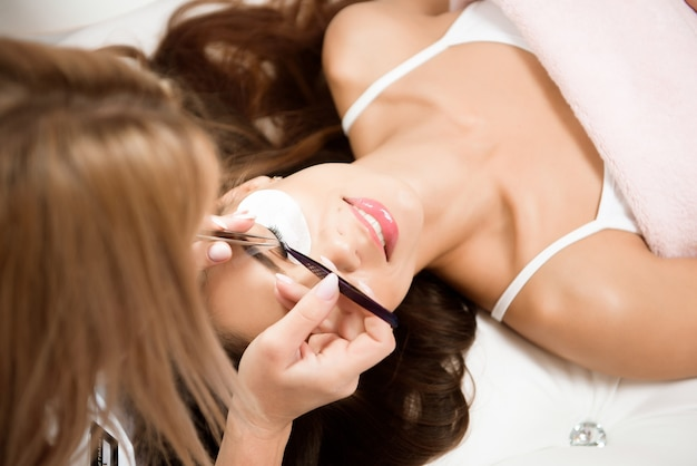 Beautiful young woman during eyelash extension in a salon.
