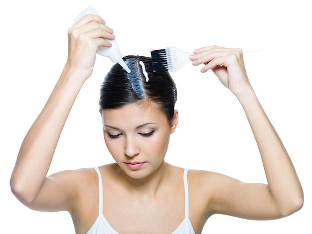 Красивая молодая женщина, окрашивающая волосы
