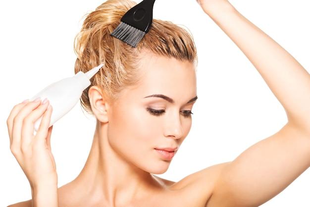 아름 다운 젊은 여자는 그녀의 머리를 염색합니다. 흰색으로 격리.
