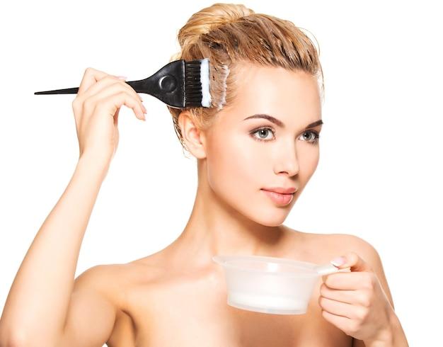 Красивая молодая женщина красит волосы. изолированные на белом.