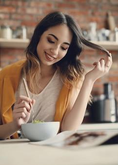 Красивая молодая женщина ест здоровый салат