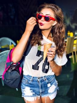 Bella giovane donna che mangia un grande gelato dolce in occhiali da sole rossi, pantaloncini, borsa sportiva sulla spalla, in piedi fuori in estate.