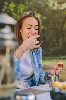 Красивая молодая женщина ест торт на завтрак доброе утро в лесу