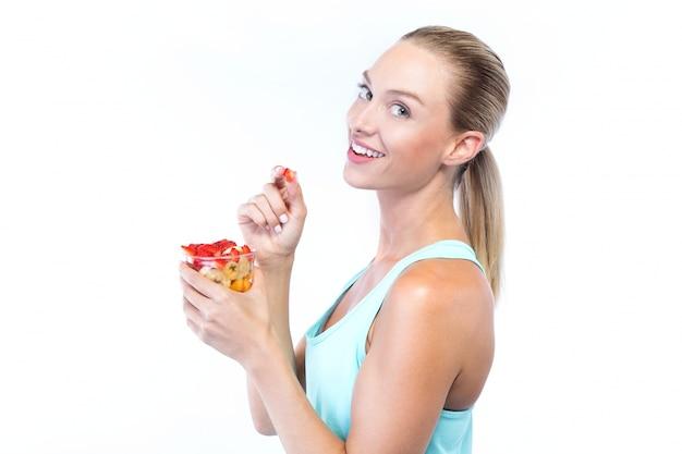 Красивая молодая женщина, есть зерновые и фрукты на белом фоне.