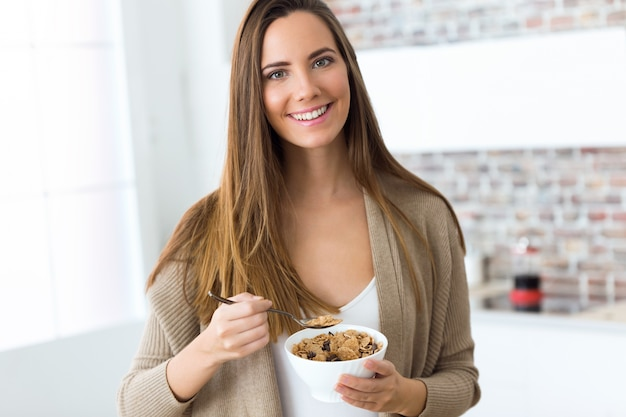 Beautiful young woman eating cereals at home.
