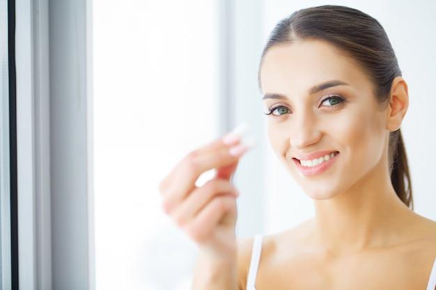 Красивая молодая женщина ест жевательную резинку, улыбаясь.