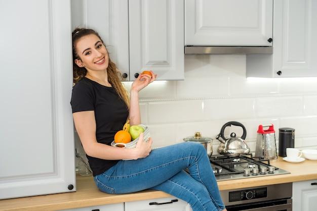 キッチン、ダイエットで早朝の朝食に新鮮な果物を食べる美しい若い女性。女性のライフスタイル