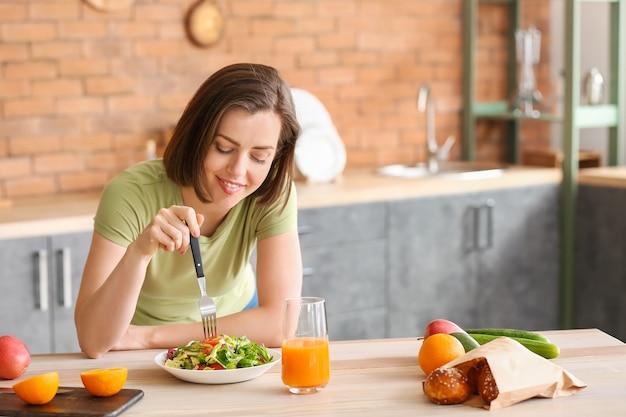 キッチンで新鮮なサラダを食べる美しい若い女性