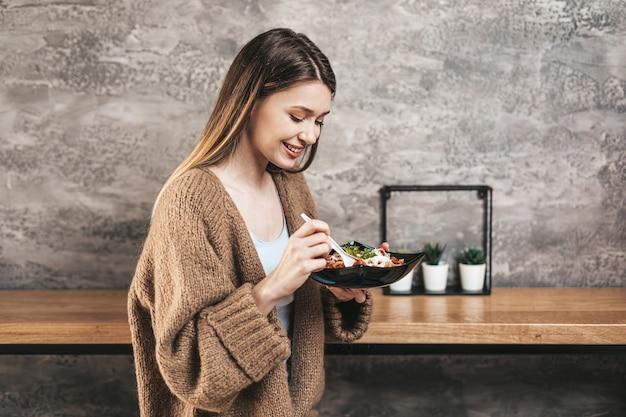 Красивая молодая женщина ест итальянские макаронные изделия.