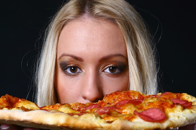 Beautiful young woman eating pizza