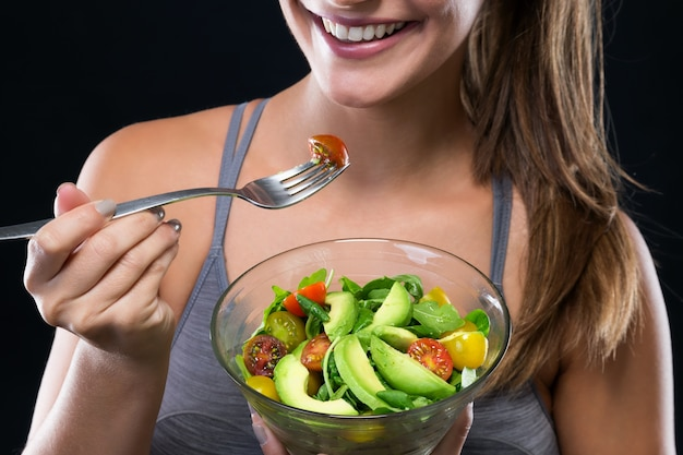 Beautiful young woman eating salad over black background.