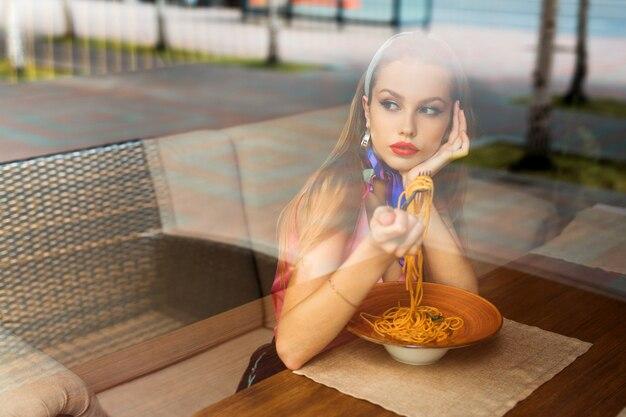 美しい若い女性がレストランでスパゲッティを食べる