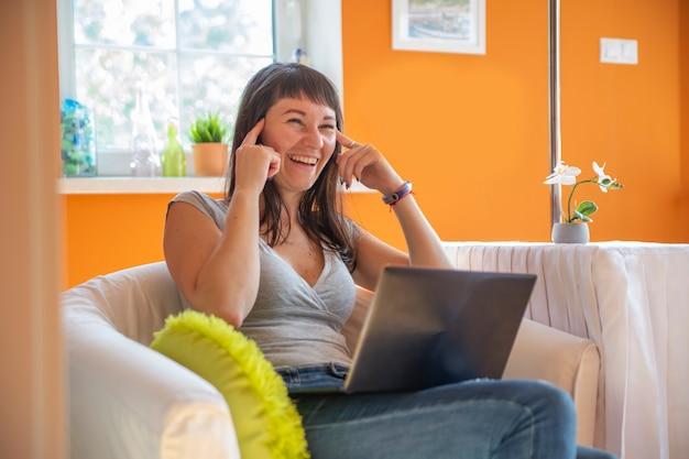 Красивая молодая женщина эмоционально смотрит на ноутбук. эмоционально удивлен и плачет об успехе.