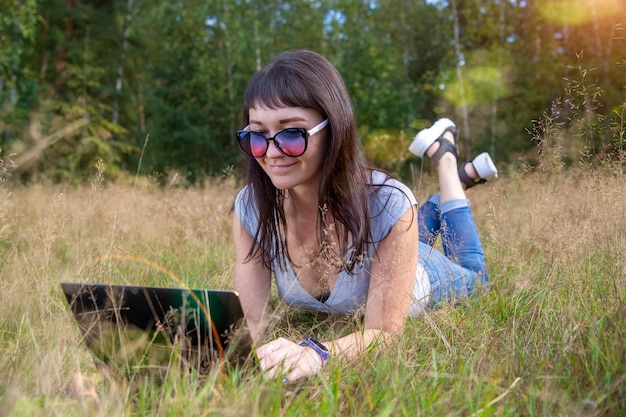 Beautiful young woman emotionally working on a laptop on a sunny lawn on a warm summer day. happy remote freelancer