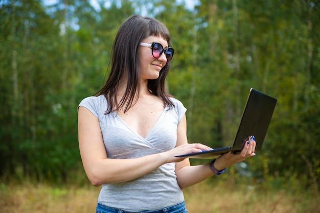Красивая молодая женщина эмоционально работает на ноутбуке на солнечной лужайке в теплый летний день. счастливый удаленный фрилансер