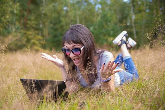 暖かい夏の日に日当たりの良い芝生の上でラップトップに感情的に取り組んでいる美しい若い女性。ハッピーリモートフリーランサー