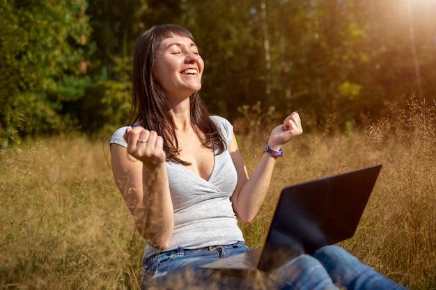 幸せな暖かい夏の日に日当たりの良い芝生の上でラップトップに感情的に取り組んでいる美しい若い女性
