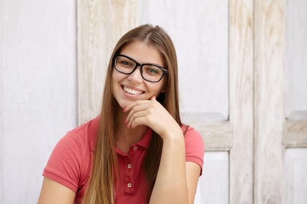 Красивая молодая женщина-сотрудник, одетая небрежно, с дружелюбной и уверенной улыбкой, держась за подбородок
