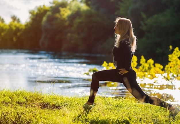Красивая молодая женщина занимается спортом на открытом воздухе у реки