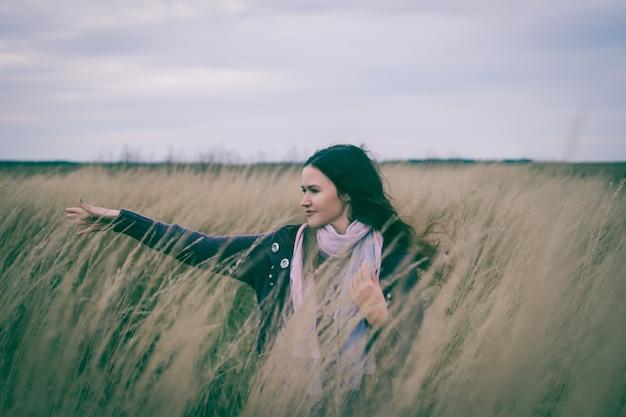 Красивая молодая женщина, наслаждаясь прогулкой в пшеничном поле. фото с копией пространства