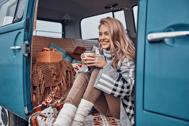 Красивая молодая женщина, наслаждаясь горячим напитком и улыбаясь, проводя время в ретро-минивэне