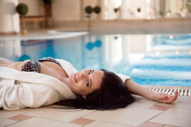 スパとプールを楽しんでいる美しい若い女性。