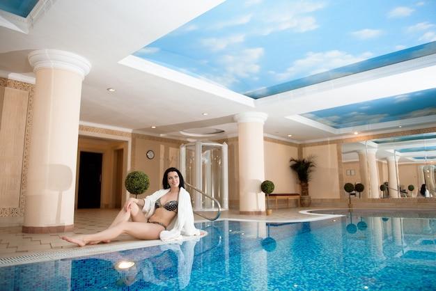 스파와 수영장을 즐기는 아름 다운 젊은 여자.