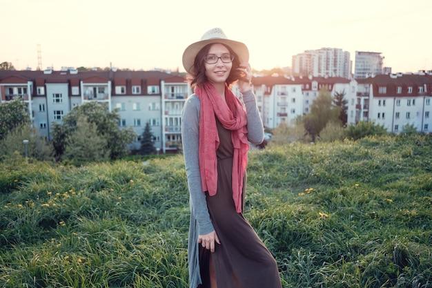 丘の上に夕日を楽しむ美しい若い女性。