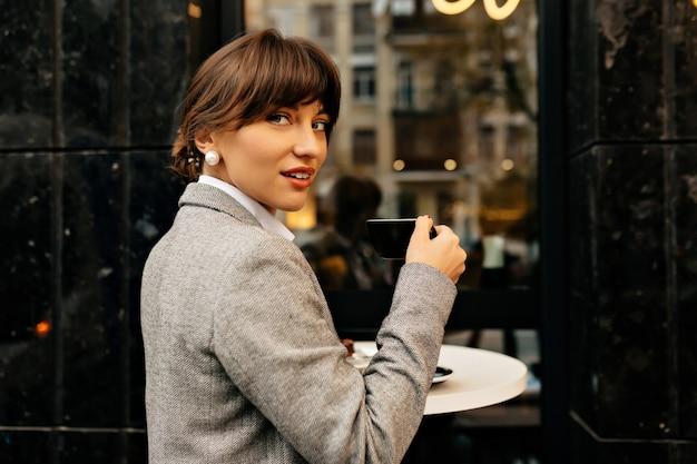 仕事の日を楽しんでいる美しい若い女性は、屋外のカフェでコーヒーブレイク、手にコーヒーを持っている陽気な女性を持っています。