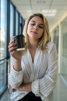 Beautiful young woman enjoys coffee and listens to music during lunch break in the corridor of a modern business center